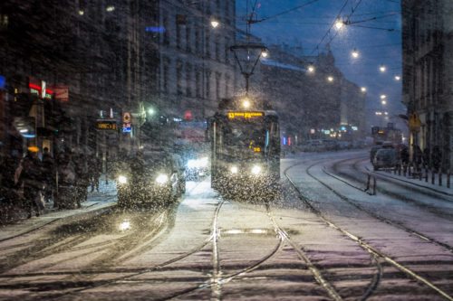 A tram and cars are seen cover in snow during a snowfall  in Krakow.