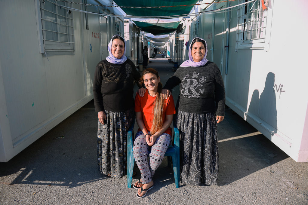 Rania (C), poses for a portrait with her stepmother, Kowath (L) and her mother, Fro (R) next to their container two days before their departure to Germany.