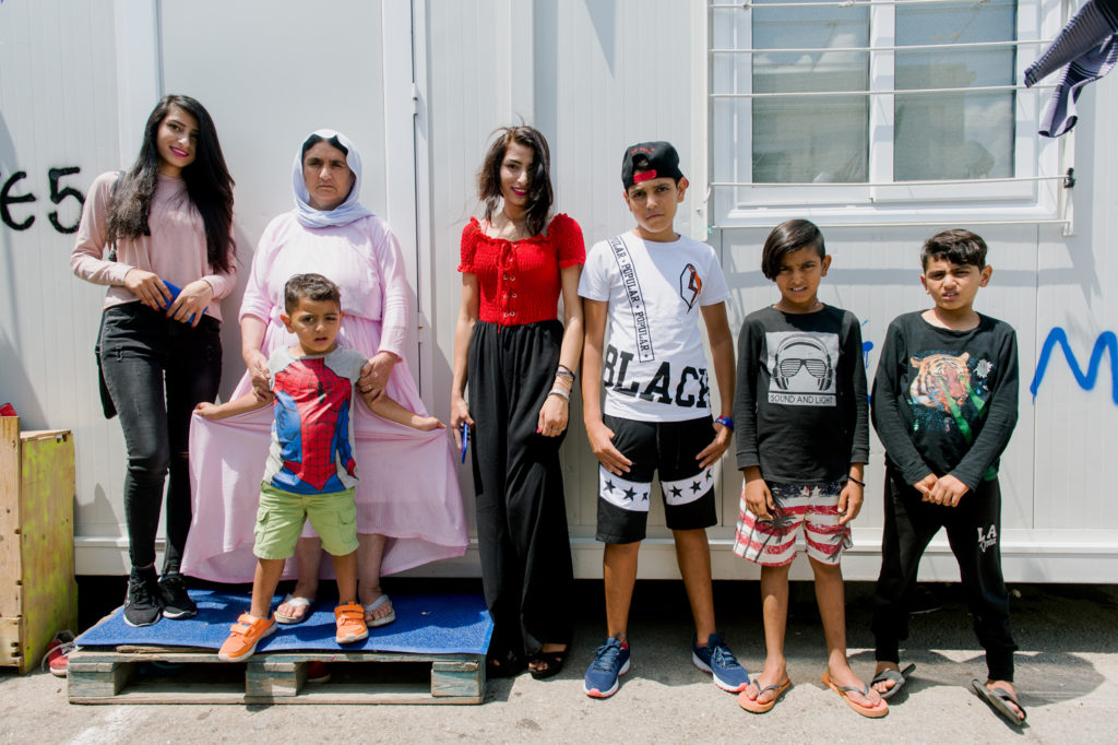 (Left to Right) Shahad, Kana, Selim, Saafa, Nahala, Kaden and Karim pose for a family photo after their interview at Skaramagas refugee camp in Athens.