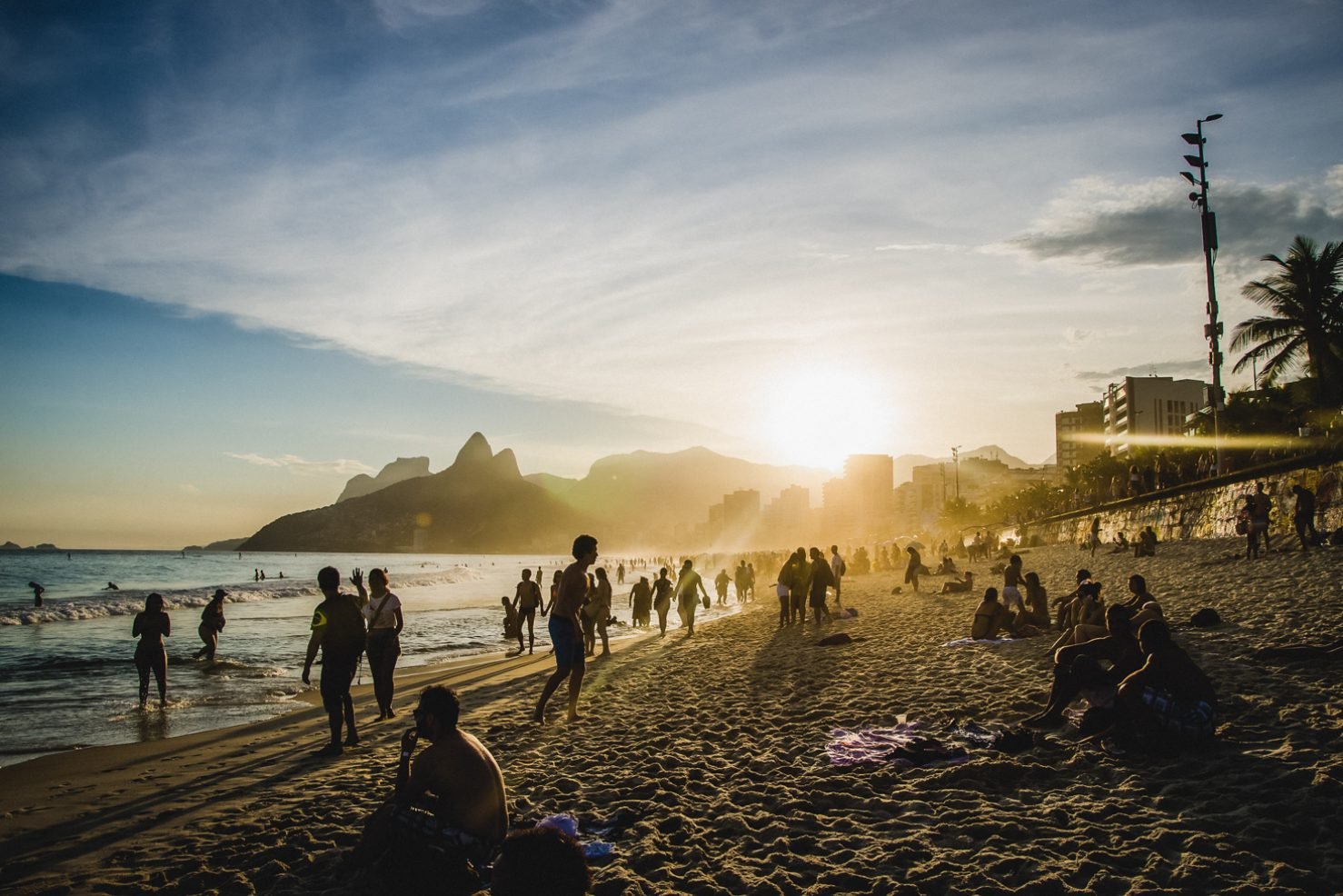 People are seen at Ipanema beach as the sun sets.